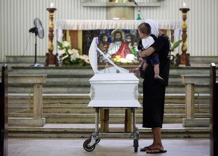 A relative carries the son of Eric Quintinita Sison during burial rites in Pasay city, metro Manila, Philippines August 31, 2016. Picture taken August 31, 2016. REUTERS/Czar Dancel