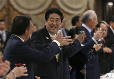 Japan's Prime Minister Shinzo Abe raises a toast with Brunei's Sultan Hassanal Bolkiah and other ASEAN countries' leaders during a welcome dinner of ASEAN-Japan Commemorative Summit in Tokyo