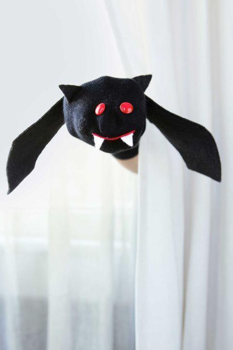 """<p>Your kid can get batty with their own handmade puppet.</p><p><strong>Step 1:</strong> Begin by sliding one hand inside a children's black crew sock, until your fingertips reach the end of the sock and its heel rests on the palm of your hand. Using our photo as a guide, determine where the ears, eyes, mouth, fangs, and wings will go; mark with chalk. Remove sock.</p><p><strong>Step 2:</strong> Hand-stitch two red button eyes in place, then hand-stitch on a single-line mouth with red embroidery floss. Cut out two black felt triangles for the ears and two white felt triangles for the fangs; hand-stitch all in place.</p><p><strong>Step 3:</strong> Cut two wings out of black felt at least 5""""W x 14""""L and hand-stitch to the sock as shown. </p>"""