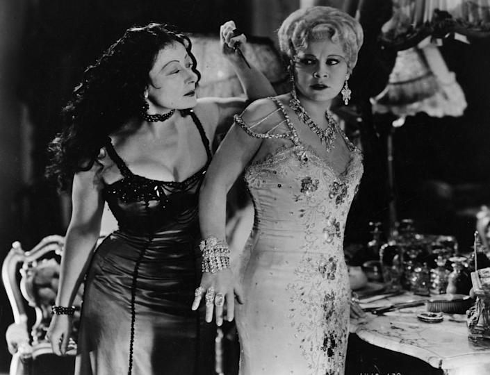 """<p>Both onscreen and off, Mae West was typically found dripping in diamonds. So what makes her bejeweled getup in <em>She Done Him Wrong</em> so iconic? The famous actress actually purchased most of the jewelry in the film herself — from the chandelier diamond earrings to her wrist (and fist) full of gems. West would <a href=""""https://www.bejeweledmag.com/neil-lane-from-collecting-to-dressing-hollywood/"""" rel=""""nofollow noopener"""" target=""""_blank"""" data-ylk=""""slk:sell most of her jewelry"""" class=""""link rapid-noclick-resp"""">sell most of her jewelry</a> to donate to the war effort, but the 1920s 40-carat diamond bracelet worn in the 1933 film remained in her collection. The stunning piece was eventually purchased by jeweler Neil Lane. </p>"""