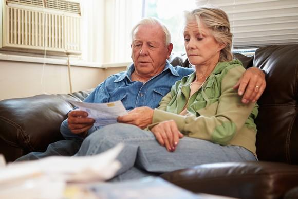 Serious senior couple seated side by side on a sofa and looking at paperwork