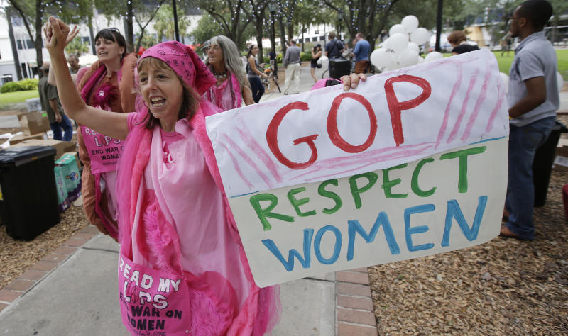Medea Benjamin of Washington, D.C. displays her sign during a Code Pink protest before Republican National Convention, Sunday, Aug. 26, 2012, in Tampa, Fla. (AP Photo/Dave Martin)