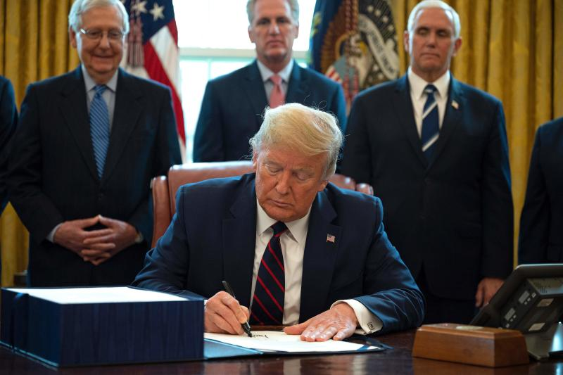 US President Donald Trump signs the CARES act, a $2 trillion rescue package to provide economic relief amid the coronavirus outbreak, at the Oval Office of the White House on March 27, 2020. - After clearing the Senate earlier this week, and as the United States became the new global epicenter of the pandemic with 92,000 confirmed cases of infection, Republicans and Democrats united to greenlight the nation's largest-ever economic relief plan. (Photo by JIM WATSON / AFP) (Photo by JIM WATSON/AFP via Getty Images)