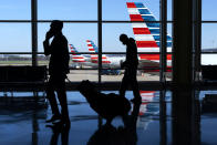 Wearing masks, travelers walk to and from their planes at Ronald Reagan Washington National Airport, Tuesday, Nov. 24, 2020, in Arlington, Va., in advance of the Thanksgiving holiday. (AP Photo/Jacquelyn Martin)
