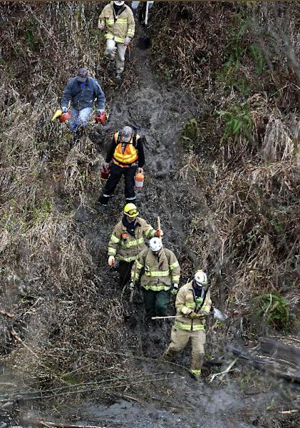 Volunteers and firefighters with chainsaws and hand tools hike down a rugged path toward the scene of a deadly mudslide, Tuesday, March 25, 2014, in Oso, Wash. At least 14 people were killed in the 1-square-mile slide that hit in a rural area about 55 miles northeast of Seattle on Saturday. Several people also were critically injured, and homes were destroyed. (AP Photo/Elaine Thompson)