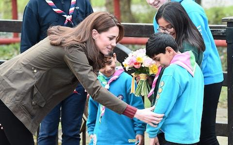 Kate admires a Scout's many badges - Credit: Getty
