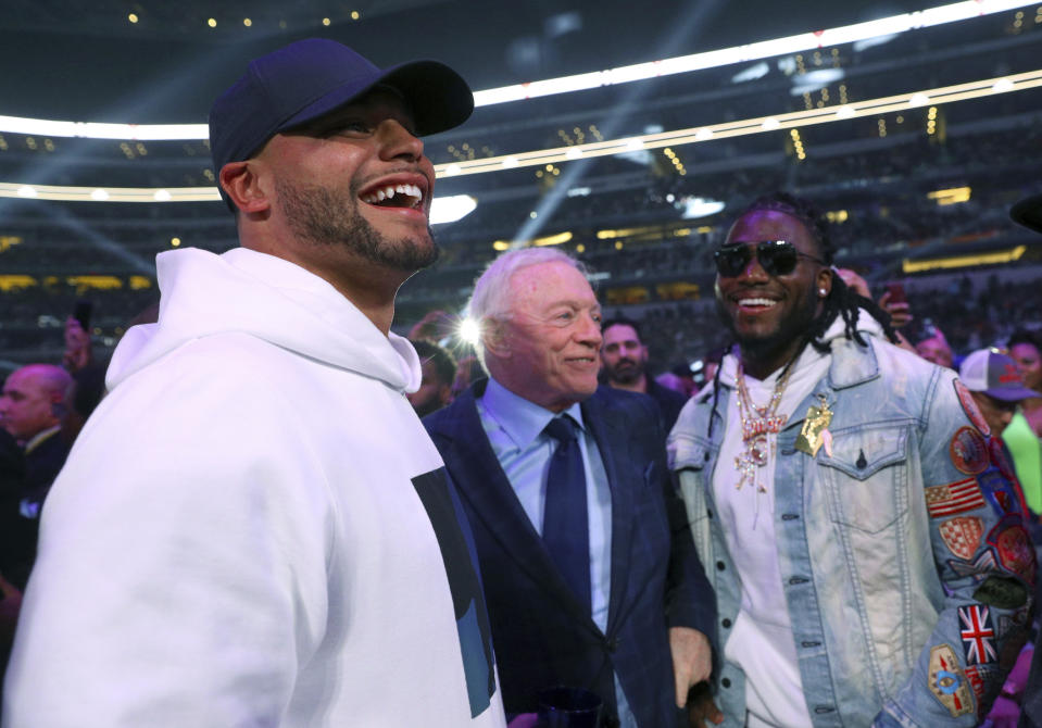 Dallas Cowboys quarterback Dak Prescott, left, team owner Jerry Jones, center, and defensive end DeMarcus Lawrence, right, visit before the main event between boxers Errol Spence Jr. and Mikey Garcia on Saturday, March 16, 2019, in Arlington, Texas. (AP Photo/Richard W. Rodriguez)