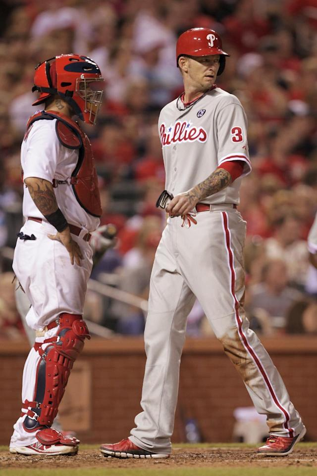 Philadelphia Phillies' A.J. Burnett (34) walks across home to score a run on a Jimmy Rollins ground-rule double, as St. Louis Cardinals catcher Yadier Molina stands nearby during the fifth inning of a baseball game, Friday, June 20, 2014, in St. Louis. (AP Photo/Tom Gannam)