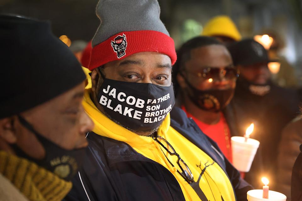jacob blake sr wears a mask that says jacob blake father son brother black man holding a candle with justin blake at his side