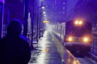 A woman waits for a Long Island Rail Road train in the Queens borough of New York as snow falls at the start of an oncoming snow storm, Wednesday, Dec. 16, 2020. (AP Photo/Frank Franklin II)