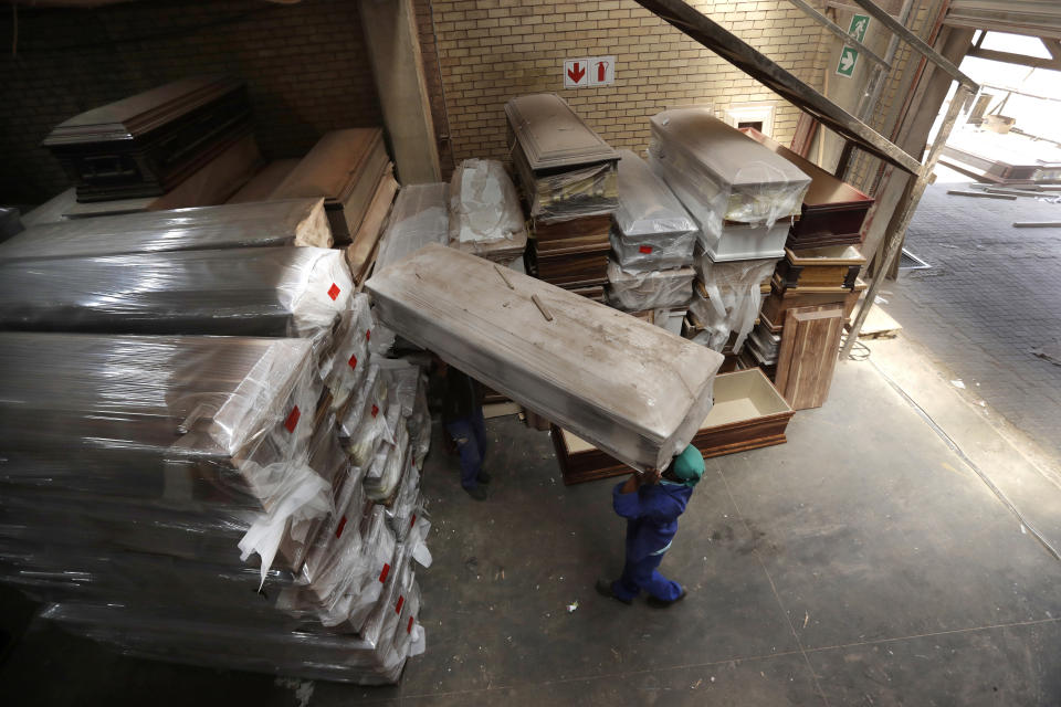 "A worker stacks coffins at at Enzo Wood Designs, in Johannesburg, Wednesday, Sept. 30. 2020. Casey Pillay, a coffin-maker in South Africa, watched the coronavirus pandemic turn his business upside down. For Pillay, the need for coffins rose and fell as South Africa's lockdown levels changed, but overall, he said, ""business went down."" As the world surpasses 1 million deaths, Africa is bracing for a likely second wave of infections. (AP Photo/Themba Hadebe)"