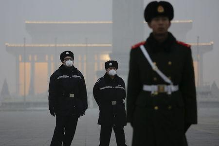 Policemen wear protective masks behind a paramilitary soldier at the Tiananmen Square on an extremely polluted day as hazardous, choking smog continues to blanket Beijing, China December 1, 2015. REUTERS/Damir Sagolj