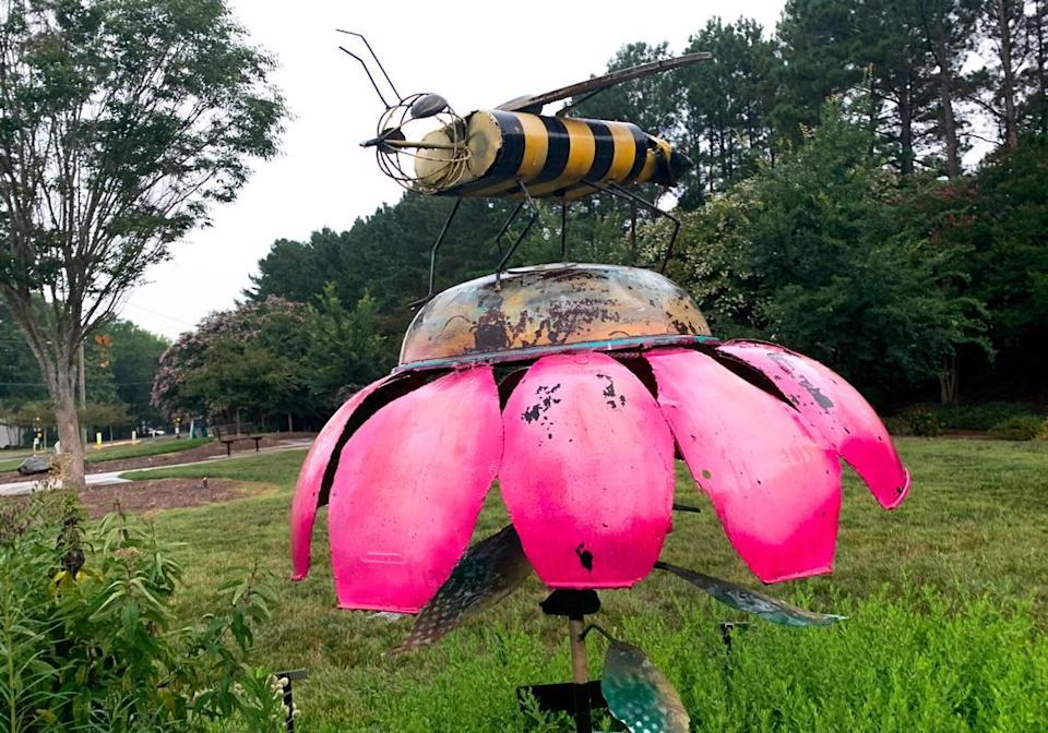 A bee statue stands at a pollinator garden in Matthews on July 26, 2021.
