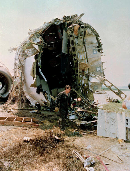 FILE- In this July 21, 1989, file photo, a National Transportation Safety Board investigator walks in front of the torn portion of the passenger compartment of the United Airlines DC-10 that crashed and exploded on landing at Sioux Gateway Airport, near Sioux City, Iowa. The plane crashed July 19. (Ed Porter/Sioux City Journal via AP, Pool)