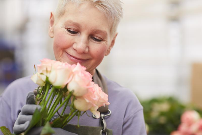 Mature gardener with short hair holding roses in her hands and smelling them