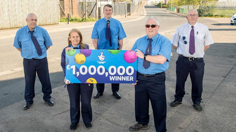 Five bus drivers are pictured with a check from EuroMillions lottery.
