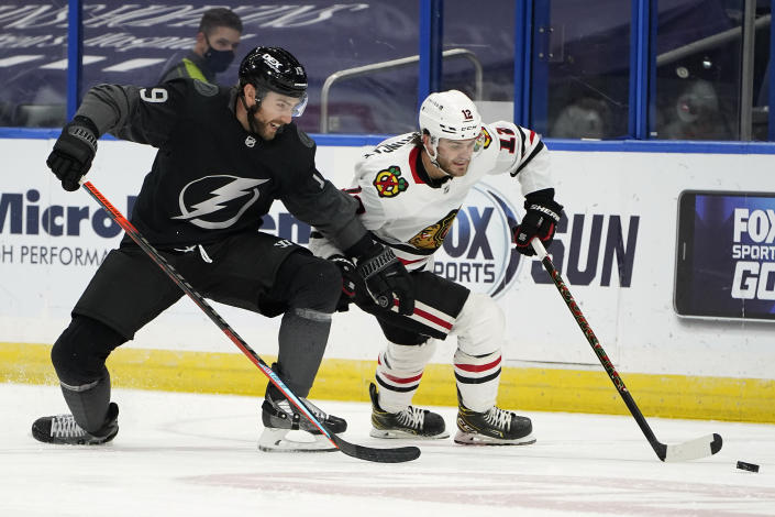 Tampa Bay Lightning right wing Barclay Goodrow (19) and Chicago Blackhawks left wing Alex DeBrincat (12) battle for the puck during the second period of an NHL hockey game Saturday, March 20, 2021, in Tampa, Fla. (AP Photo/Chris O'Meara)
