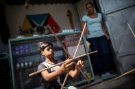 A boy builds a kite as the Petare neighbourhood celebrates the 400th anniversary of its founding, in Caracas