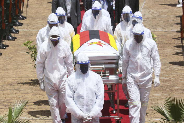"""burial of Dr Ellen Gwaradzimba who died of COVID-19, at the Heroes Acre in Harare, Thursday, Jan. 21, 2021. Zimbabwean President Emmerson Mnangagwa who presided over the burial called the pandemic """"evil"""" and urged people to wear masks, practice social distancing and sanitize, as cases across the country increased amid a fragile health system. (AP Photo/Tsvangirayi Mukwazhi)"""
