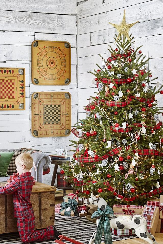 """<p>Lean into the colors of the season by wrapping a red and green plaid ribbon around the entire tree. </p><p><a class=""""body-btn-link"""" href=""""https://www.amazon.com/Morex-Ribbon-Festival-Fabric-50-Yard/dp/B00A23JZME/?tag=syn-yahoo-20&ascsubtag=%5Bartid%7C10055.g.2707%5Bsrc%7Cyahoo-us"""" target=""""_blank"""">SHOP RIBBON</a></p><p><em><a href=""""https://www.countryliving.com/home-design/decorating-ideas/tips/g1251/trim-christmas-trees-1208/"""" target=""""_blank"""">Get the tutorial at Country Living »</a></em></p>"""
