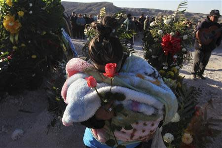 A woman holds roses during the funeral of Idaly Jauche Laguna in Ciudad Juarez December 27, 2013. REUTERS/Jose Luis Gonzalez