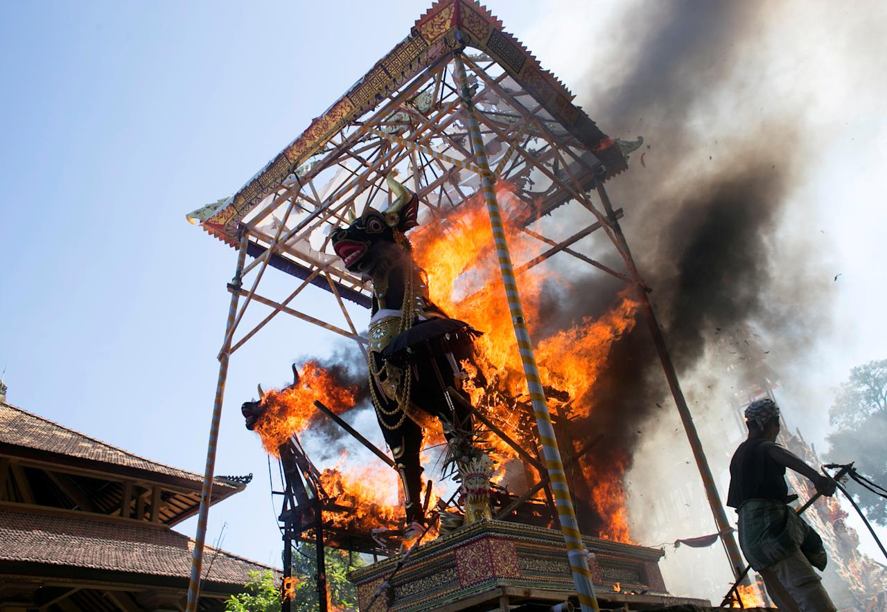 Balinese Hindu man burns bull coffins remaining of Ubud royal family members during a cremation ceremony in Gianyar, Bali, Indonesia, April 22, 2019. REUTERS/Johannes P. Christo  TPX IMAGES OF THE DAY