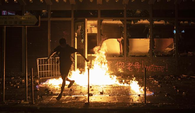 A protester runs after setting a government office building on fire in Hong Kong on Tuesday. Demonstrations spread across the city as Beijing celebrated the 70th anniversary of the founding of the People's Republic of China. Photo: AP