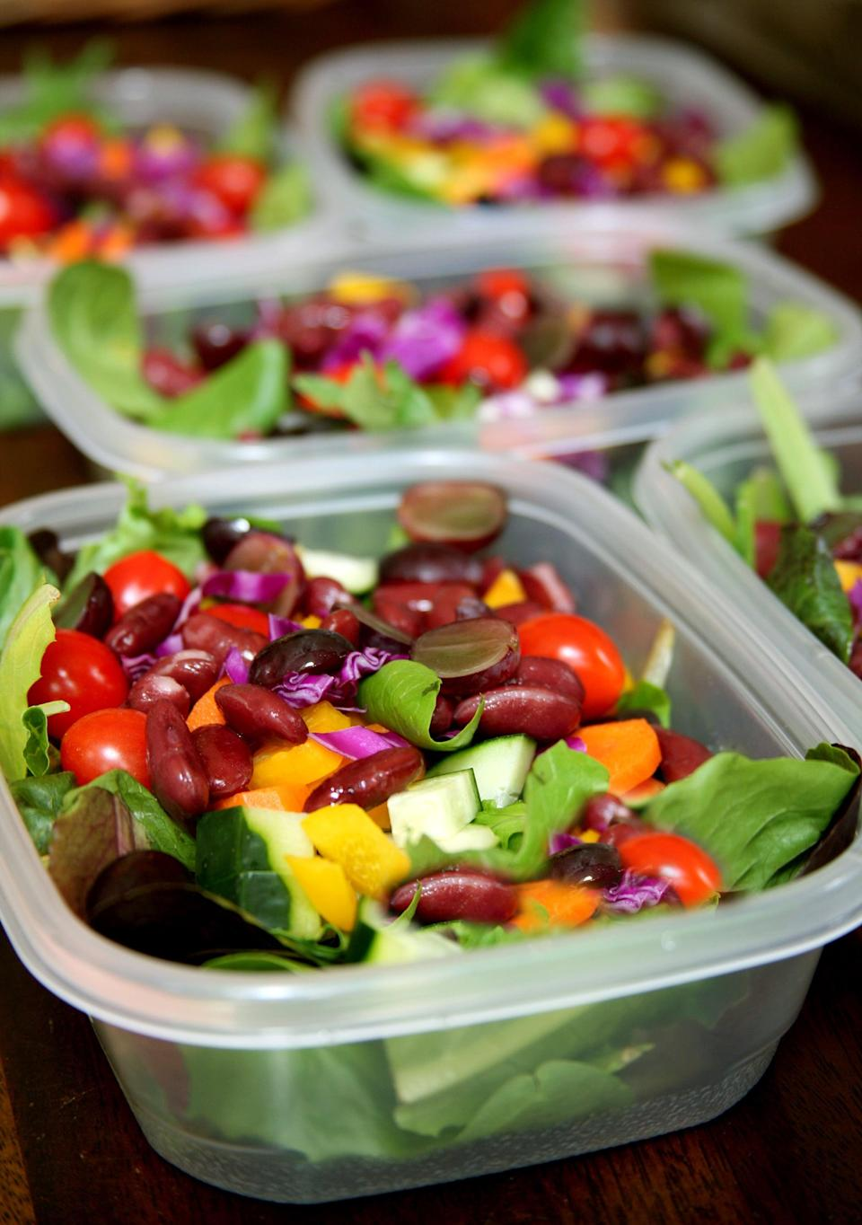 """<p>Choose plastic containers that are flat and rectangular in shape. These not only stack well in your fridge, but they also create more space for the veggies to spread out, preventing sogginess. This method keeps salads fresh for five days. </p> <ol> <li><strong>Start with the greens.</strong> To save time, pick up a package of prewashed salad greens. If you're using greens from your garden or a farmers market, just make sure they're completely dry before packing. Fill the container about three-quarters full of greens (about two to three cups). </li> <li><strong>Add the veggies, beans, and fruit.</strong> Go for carrots, cucumbers, tomatoes (use cherry and keep them whole), peppers, broccoli, chickpeas, kidney beans, corn, peas, or even fruit like grapes or blueberries - whatever your little salad-loving heart desires. Drying off each ingredient with a paper towel will keep them crisper longer. </li> <li><strong>Add protein.</strong> For protein sources like marinated tofu, grilled chicken, hard-boiled eggs, certain types of cheese like cubed cheddar, and cooked (and cooled) whole grains like quinoa or brown rice, add these on top of the first three salads only (Monday's, Tuesday's, and Wednesday's). Then on Wednesday night, add protein to Thursday's and Friday's containers. Do the same with avocado, nuts and seeds, or very wet fruits like sliced strawberries.</li> <li><strong>Keep dressing separate until the moment you eat your salad.</strong> Purchase a couple dip-size containers (I'm a fan of these small <a href=""""https://www.popsugar.com/fitness/photo-gallery/7104018/image/7465345/Kids-Konserve"""" class=""""link rapid-noclick-resp"""" rel=""""nofollow noopener"""" target=""""_blank"""" data-ylk=""""slk:stainless steel containers from Kids Konserve"""">stainless steel containers from Kids Konserve</a>). Or if you have an office fridge, keep a bottle of dressing there. </li> </ol>"""