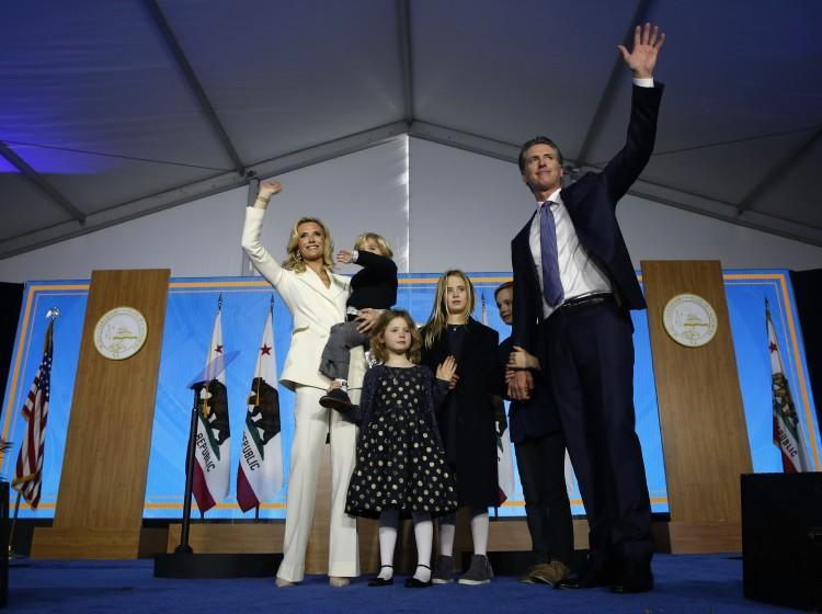 FILE -- In this Jan. 7, 2019, file photo California Governor Gavin Newsom his wife, Jennifer Siebel Newsom, and their children wave after taking the oath office during his inauguration as 40th Governor of California, in Sacramento, Calif. Newsom's office said, Tuesday, July 27, 2021, that he pulled his children out of summer camp after children at the camp weren't wearing face masks, a violation of state policy. (AP Photo/Rich Pedroncelli, File)