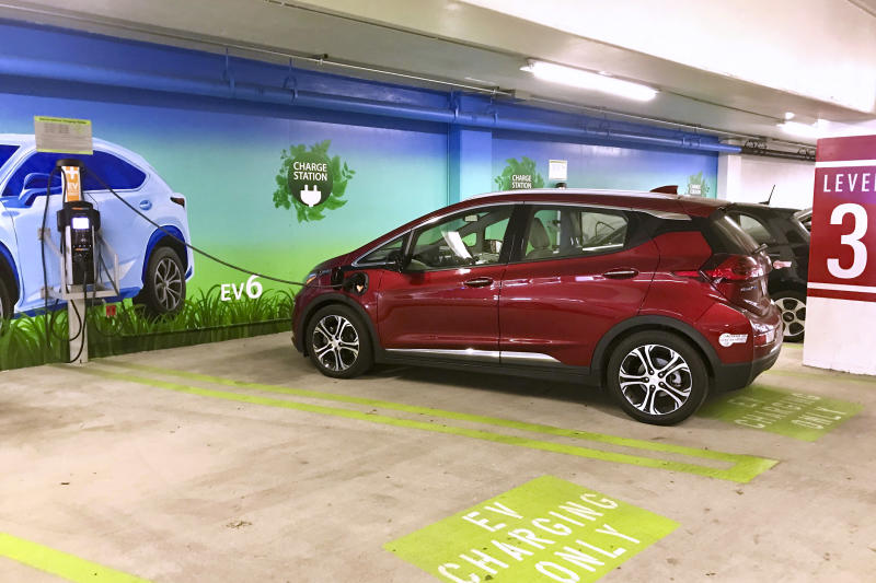 This undated photo provided by Edmunds shows a 2017 Chevrolet Bolt at a charging station in a shopping mall parking lot. You'll want to coordinate your charges with other activities to help pass the time. (Ronald Montoya/Edmunds via AP)