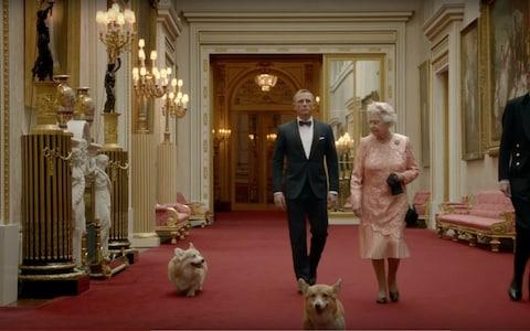 Daniel Craig and Queen Elizabeth II with two corgis and a footman during the film shown as part of the London 2012 Olympic Games opening ceremony - Credit: Videograb