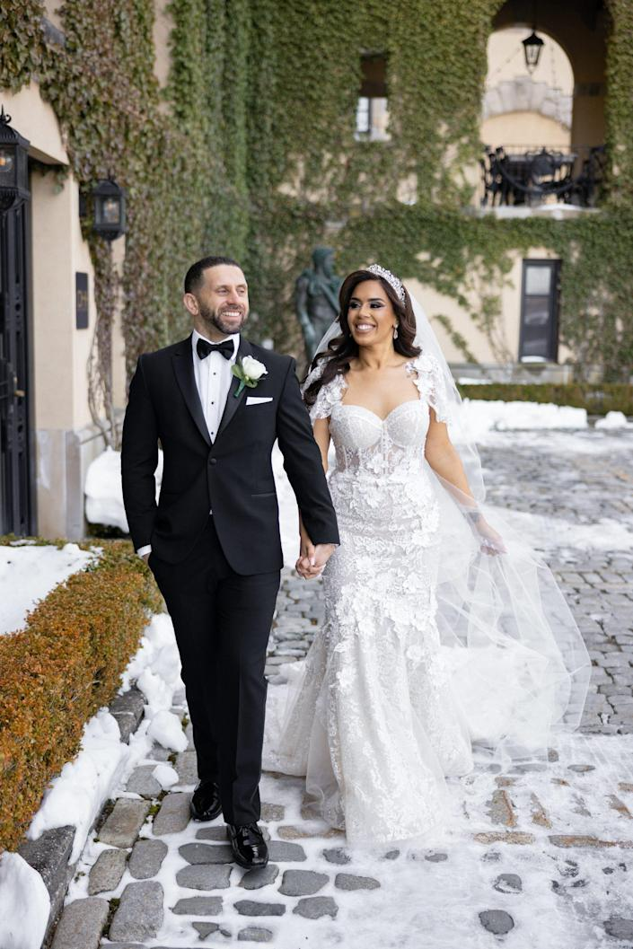 Vishnell and her husband walk on a snowy walkway on their wedding day