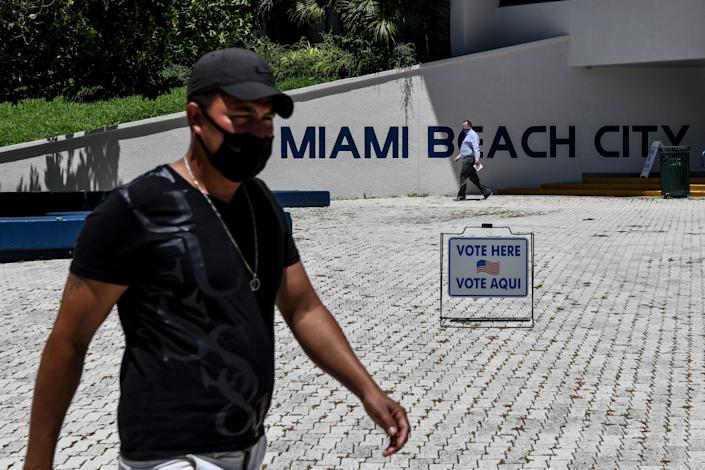 People walk past a poling centre during Florida Primary Election amid the coronavirus pandemic, in Miami Beach, Florida on August 18, 2020. (Chandan Khanna /AFP via Getty Images)
