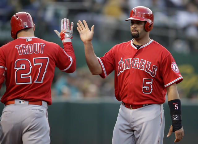 Los Angeles Angels' Albert Pujols, right, celebrates with Mike Trout (27) after scoring against the Oakland Athletics in the second inning of a baseball game, Tuesday, May 28, 2019, in Oakland, Calif. (AP Photo/Ben Margot)
