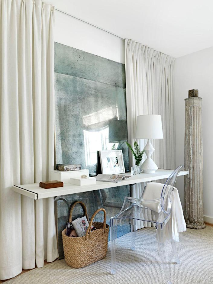 <p>Designed by Lindsey Bond, this workspace feels modern yet laidback and features a floating desk secured to the wall in a main bedroom. An antiqued mirror reflects light and makes the room feel larger, while the ghost chair keeps bulky furniture to a minimum for a wide-open feel. Follow Bond's lead and upholster your floating shelf in leather, then add some nailhead trim for a tailored look. </p>