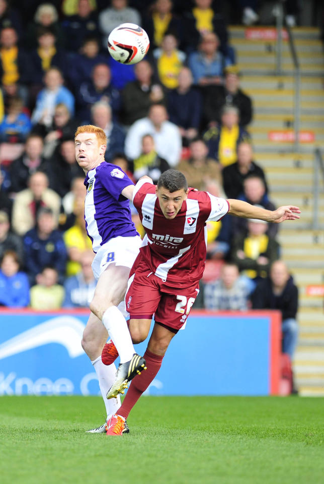 Cheltenham's James Wilson and Oxford's David Kitson (left) in action during the Sky Bet League Two match at the Abbey Business Stadium, Cheltenham.