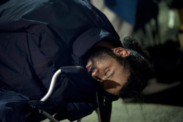 A job seeker sleeps in a lawn chair as he waits in front of the training offices of Local Union 46, a union representing metallic lathers and reinforcing ironworkers, in the Queens borough of New York, April 30, 2012.