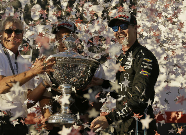 FILE - In this Sept. 17, 2017, file photo, Josef Newgarden, right, stands and celebrates after being presented the Astor Cup for winning the IndyCar championship in Sonoma, Calif. Looking on at center behind the trophy is team owner Roger Penske. Newgarden wouldnt change the career path he has had through eight IndyCar seasons, even though the American driver wanted more success earlier. (AP Photo/Eric Risberg, File)
