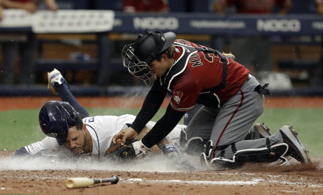 Tampa Bay Rays' Tommy Pham, left, gets tagged out by Arizona Diamondbacks catcher John Ryan Murphy at home plate while trying to score on an RBI-single by Kevin Kiermaier during the ninth inning of a baseball game, Wednesday, May 8, 2019, in St. Petersburg, Fla. (AP Photo/Chris O'Meara)