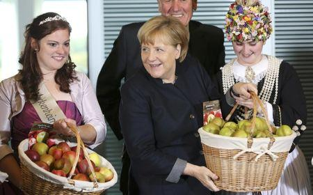 German Chancellor Merkel carries an apple basket as she poses with German 'Apple and Flower Queens'  in Berlin