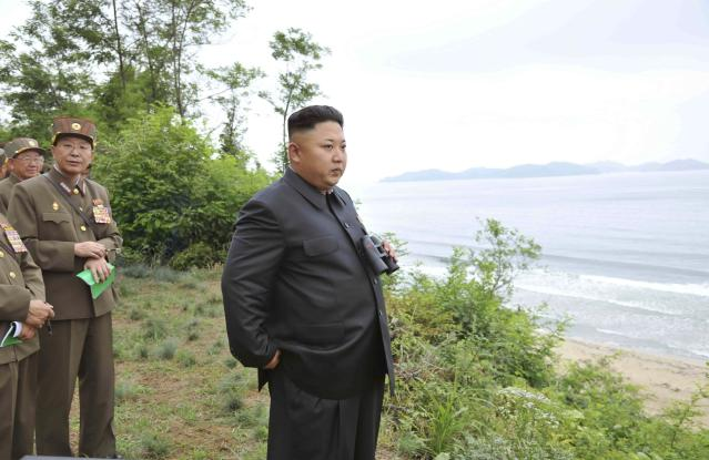 North Korean leader Kim Jong Un (R) stands with a pair of binoculars during a landing drill of the Army Ground, Naval, Air and Anti-Air forces of the Korean People's Army (KPA) in this undated photo released by North Korea's Korean Central News Agency (KCNA) in Pyongyang July 5, 2014. REUTERS/KCNA (NORTH KOREA - Tags: POLITICS MILITARY) ATTENTION EDITORS - THIS PICTURE WAS PROVIDED BY A THIRD PARTY. REUTERS IS UNABLE TO INDEPENDENTLY VERIFY THE AUTHENTICITY, CONTENT, LOCATION OR DATE OF THIS IMAGE. FOR EDITORIAL USE ONLY. NOT FOR SALE FOR MARKETING OR ADVERTISING CAMPAIGNS. THIS PICTURE IS DISTRIBUTED EXACTLY AS RECEIVED BY REUTERS, AS A SERVICE TO CLIENTS. NO THIRD PARTY SALES. NOT FOR USE BY REUTERS THIRD PARTY DISTRIBUTORS. SOUTH KOREA OUT. NO COMMERCIAL OR EDITORIAL SALES IN SOUTH KOREA