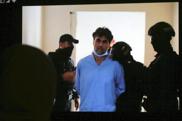 Sharif Hassan bin Zaid, one of two former officials accused of helping Jordanian Prince Hamzah try to overthrow his half-brother King Abdullah II, appears on a mobile phone screen as he is escorted by security personnel during a verdict hearing at a state security court, in Amman, Jordan, Monday, July 12, 2021. The court sentenced the two to 15 years in prison. Bassem Awadallah, who has U.S. citizenship and once served as a top aide to King Abdullah II, and Sharif Hassan bin Zaid, a member of the royal family, were found guilty of sedition and incitement charges. (AP Photo/Raad Adayleh)
