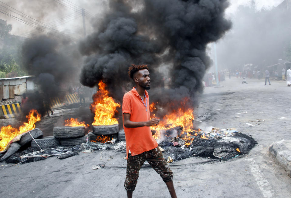 A Somali man protests against the killing Friday night of at least one civilian during the overnight curfew, which is intended to curb the spread of the new coronavirus, on a street in the capital Mogadishu, Somalia Saturday, April 25, 2020. A police officer in Somalia's capital has been arrested in the fatal shooting of at least one civilian while enforcing coronavirus restrictions, a fellow police officer said, sparking protests that continued Saturday with crowds of angry young men burning tires and demanding justice. (AP Photo/Farah Abdi Warsameh)