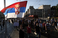 A women waves with Serbian nation flag as people gather for a demonstration in Belgrade, Serbia, Wednesday, July 8, 2020. Serbia's president Aleksandar Vucic backtracked Wednesday on his plans to reinstate a coronavirus lockdown in Belgrade after thousands protested the move and violently clashed with the police in the capital. (AP Photo/Darko Vojinovic)