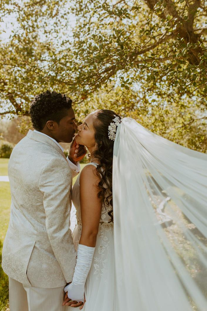 A bride and groom kiss as her veil flies up in front of trees.