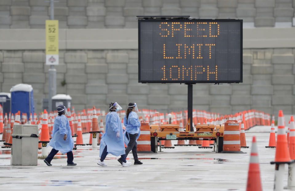 Healthcare workers walk past rows of traffic cones and a speed limit sign, Wednesday, Aug. 5, 2020, at a COVID-19 testing site outside Hard Rock Stadium in Miami Gardens, Fla. State officials say Florida has surpassed 500,000 coronavirus cases. Meanwhile, testing is ramping up following a temporary shutdown of some sites because of Tropical Storm Isaias. (AP Photo/Wilfredo Lee)
