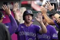 Colorado Rockies' Ryan McMahon is congratulated by teammates in the dugout after scoring on a single by Elias Diaz during the third inning of a baseball game against the Los Angeles Angels Tuesday, July 27, 2021, in Anaheim, Calif. (AP Photo/Mark J. Terrill)