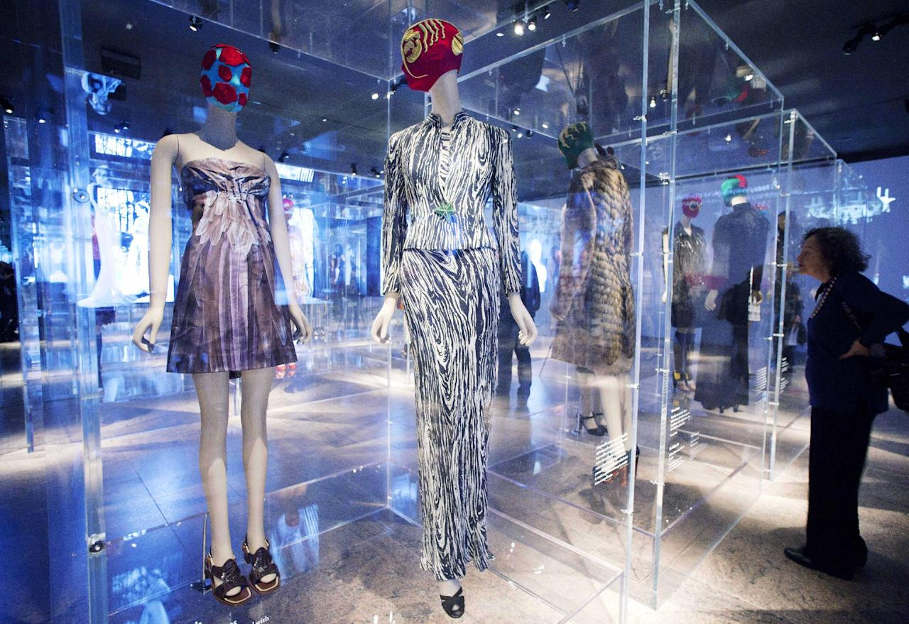 """A 2005 dress, left, by Miuccia Prada, and a 1938 ensemble, center, by Elsa Schiaparelli are displayed at the Metropolitan Museum of Art, Monday, May 7, 2012 in New York. The show """"Schiaparelli and Prada, Impossible Conversations,"""" opens May 10 and continues through Aug. 19. (AP Photo/Mark Lennihan)"""