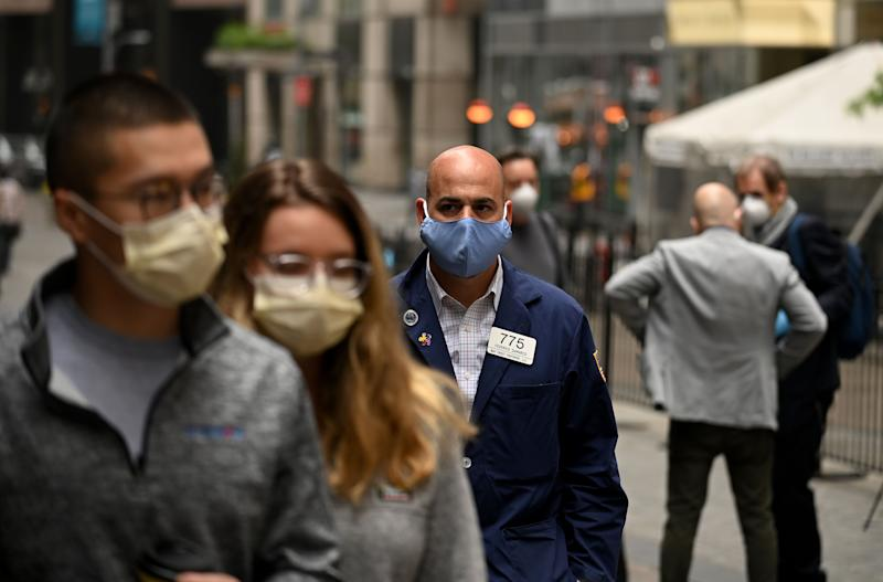 A trader walks in front of the New York Stock Exchange (NYSE) on May 26, 2020 at Wall Street in New York City. - Wall Street stocks surged early May 26, 2020 on optimism about coronavirus vaccines as the New York Stock Exchange resumed physical floor trading for the first time since late March. About five minutes into trading, the Dow Jones Industrial Average was up 2.3 percent at 25,023.76. The broad-based S&P 500 gained 2.0 percent to 3,013.04, while the tech-rich Nasdaq Composite Index advanced 1.6 percent to 9,468.96.The gains came after a ceremony presided over by New York Governor Andrew Cuomo, who wore a mask as he rung the opening bell to signal the start of the day for traders, also clad in masks and separated by plexiglas. (Photo by Johannes EISELE / AFP) (Photo by JOHANNES EISELE/AFP via Getty Images)