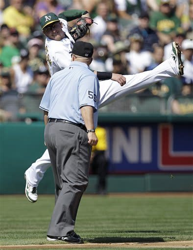 Oakland Athletics third baseman Josh Donaldson misses a throw allowing Seattle Mariners' John Jaso to score in the second inning of a baseball game Saturday, Sept. 29, 2012, in Oakland, Calif. At right is third base umpire Eric Cooper. (AP Photo/Ben Margot)
